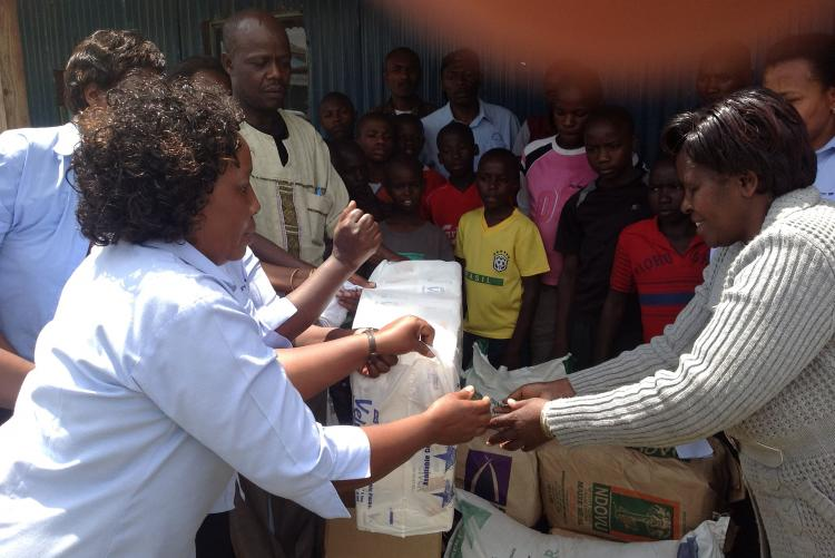 Ms. Susane Ngugi and Mr. Henry EdewaPresenting the goods to the children